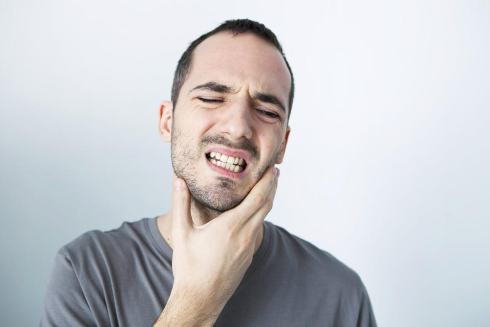 Man holding jaw from TMJ pain