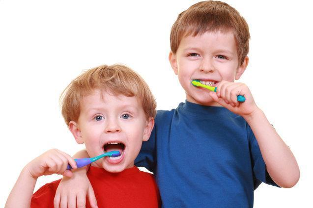 two young brothers brushing teeth