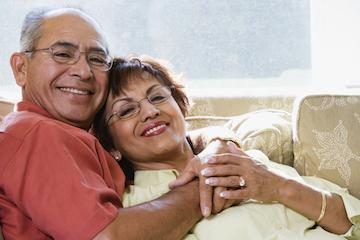 Older couple snuggling on couch | Dentist Burnaby BC