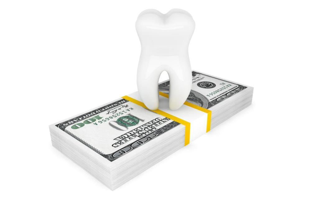 Tooth sitting on top of stack of money | Dentist Burnaby BC