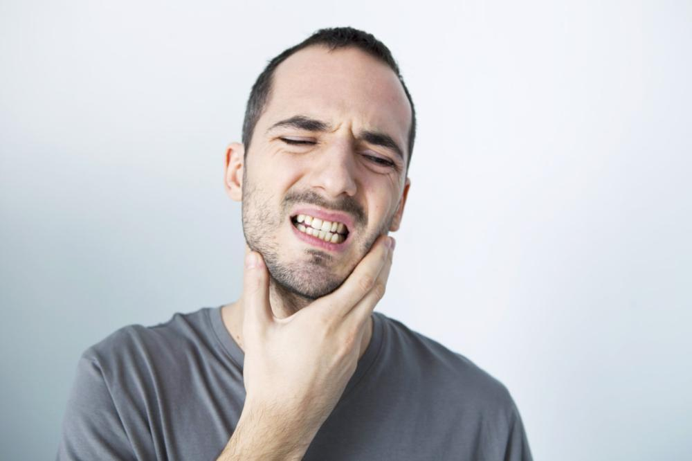 Person holding cheek with toothache | Dentist Burnaby BC