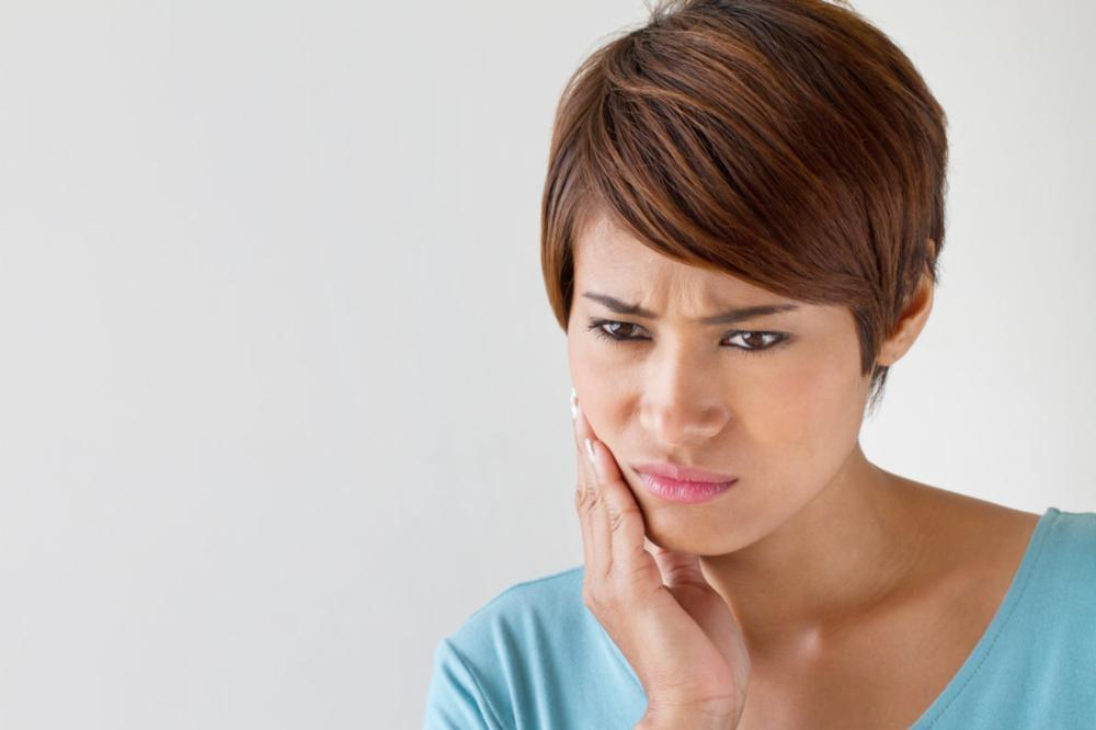 Woman holding jaw in pain | Dentist Burnaby bC