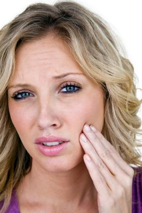 Woman holding jaw in pain | Central Park Dental Clinic