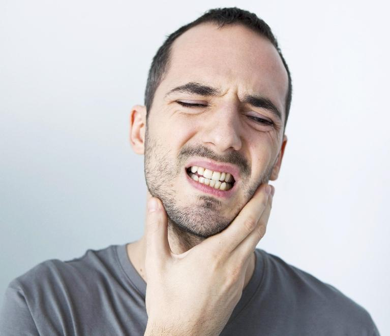 Man holding jaw in pain | Burnaby BC Dentist