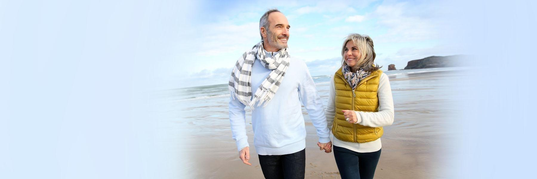 Older Couple walking on beach | Burnaby BC Dentist
